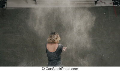 Rear View of a dancer girl who moving in cloud of white dust or powder on gray background at studio. Female ballet dancer in black body suit perform on stage in theater and using white powder or white smoke dust