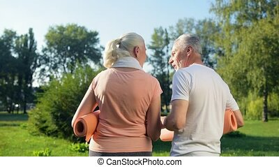 Rear view of a delighted eldelry sporty couple walking in the park