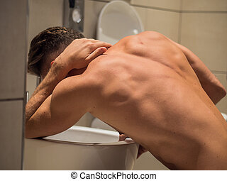 Drunk Young Man Vomiting in the Toilet at Home
