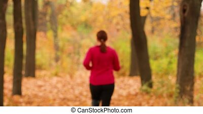 Rear view of fat girl doing cardio jogging in the autumn forest of a city park for marathon and fitness.