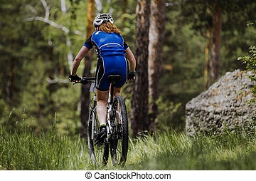 rear view of a female cyclist riding