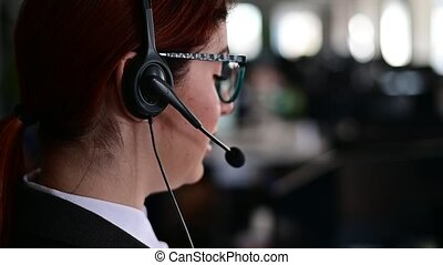 Rear view of a female help desk operator. An office manager with a headset answers customer calls. Unrecognizable woman in glasses works as a secretary. Employee call center.