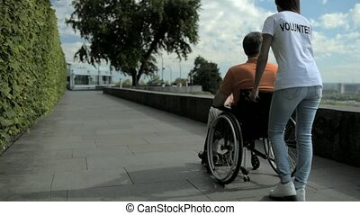 Rear view of a female volunteer walking with a wheelchaired man