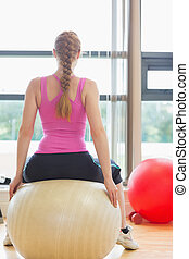 Rear view of a fit woman sitting on exercise ball