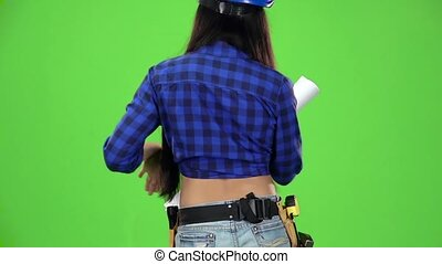 Rear view of a girl in a shirt with a drawing coming on a green background. Slow motion. Close up