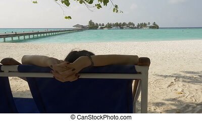 Rear view of a girl on a lounger, female hands. Sea, beach, vacation