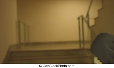 Rear view of a male athlete running up staircase indoor building