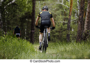 rear view of a male cyclist riding