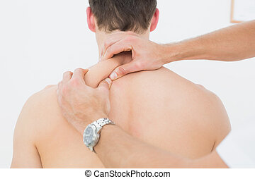 Rear view of a man being massaged by a physiotherapist -...