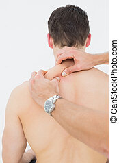 Rear view of a man being massaged by a physiotherapist - ...