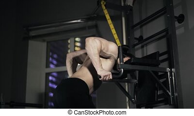 Rear view of a man doing push ups on parallel bars in a gym