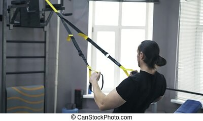 Rear view of a man doing push ups with gymnastic rings -...