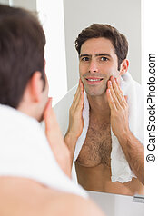 Rear view of a man looking at self in bathroom mirror