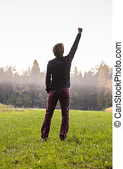 Rear view of a man standing in green meadow with one arm lifted in the air