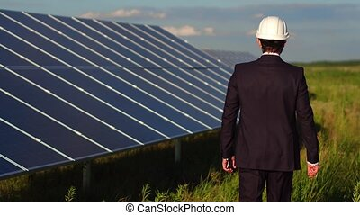 Rear view of a man walking in field where solar panels are installed.