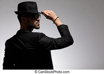 Rear view of a mysterious casual man adjusting his cap