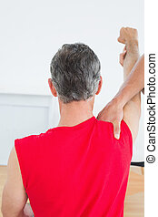 Rear view of a physiotherapist massaging mature mans arm