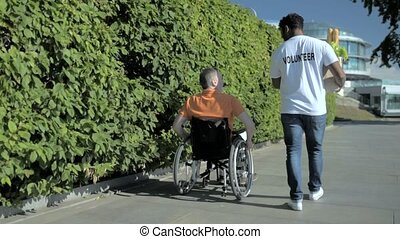 Rear view of a pleasant volunteer helping a wheelchaired man