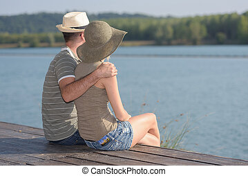 rear view of a romantic couple sitting on the pier