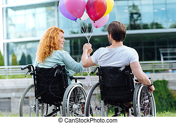 Rear view of a senior couple in the wheelchairs holding balloons