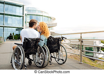 Rear view of a senior wheelchaired couple kissing