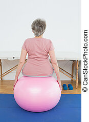 Rear view of a senior woman sitting on yoga ball