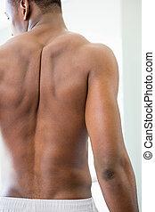 Rear view of a shirtless muscular man