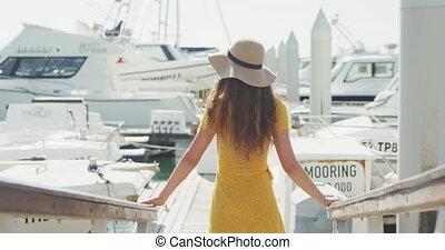 Rear view of a teenage Caucasian girl enjoying harbor side...