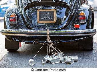 Rear view of a vintage car with just married sign and cans attached