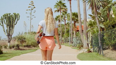 Rear View of a Woman Carrying Skateboard