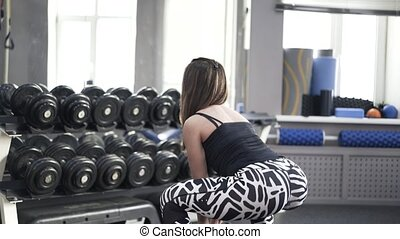 Rear view of a woman doing a dumbbell exercise in a gym