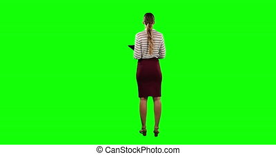 Rear view of a woman holding a digital tablet with green screen