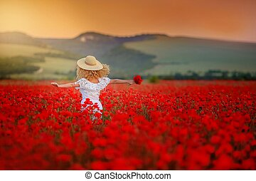 Rear view of a woman in a field with red poppies