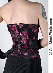 Rear view of a woman in black corset with floral embroidery