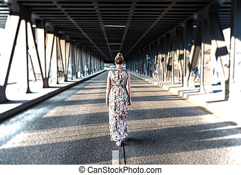 rear view of a woman in long dress walking in the middle of a road under bridge