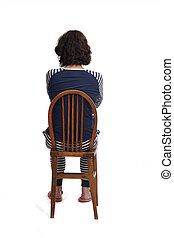 rear view of a woman in pajamas sitting o a chair on white background, arms crossed