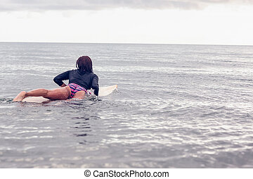 Rear view of a woman on surfboard in water