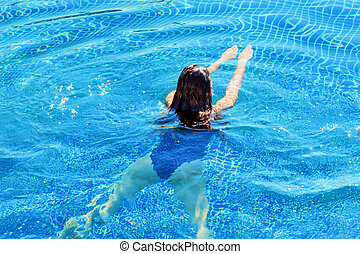 Rear view of a woman swimming. Swim and fitness