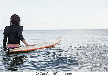 Rear view of a woman with surfboard in the water