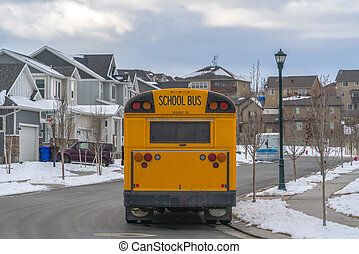 Rear view of a yellow school bus with a window and several signal lights