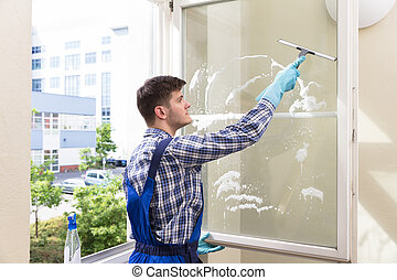 Rear View Of A Young Male Housekeeper Cleaning Window