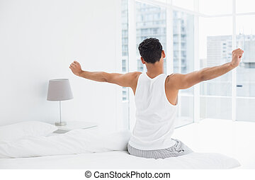 Rear view of a young man stretching arms in bed