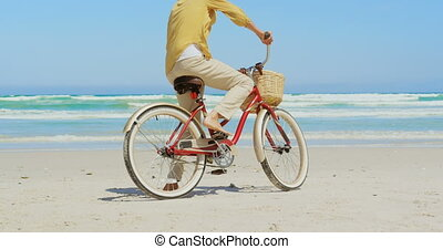 Rear view of active senior African American woman standing with bicycle on beach in the sunshine 4k