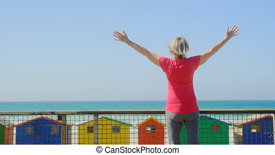 Rear view of active senior Caucasian woman standing with ...