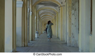 Rear view of adult woman in coat walking down stone terrace arched corridor