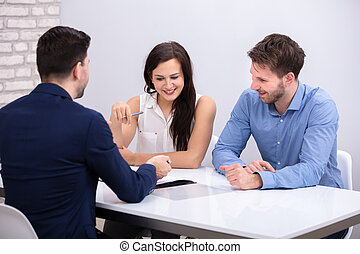 Advisor Sitting With Smiling Young Couple