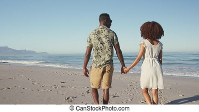 Rear view of African American couple walking side by side at...