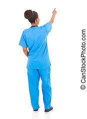 rear view of african american nurse pointing empty space