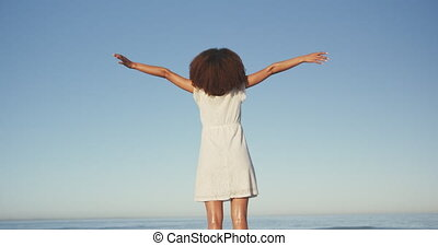 Rear view of an African American woman enjoying time in the sun, standing on a tropical beach and raising her arms, looking out to sea with clear blue sky in the background, in slow motion