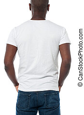 Back view of man looks ahead, hands in pocket